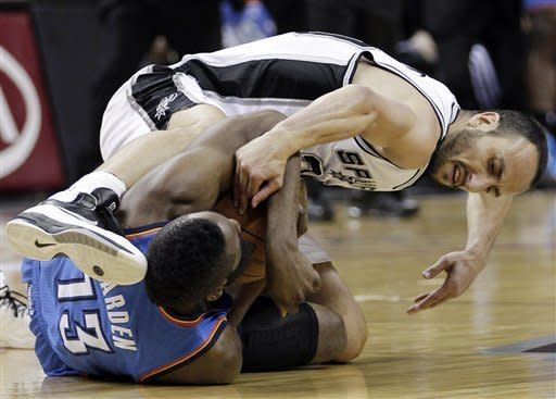 Oklahoma City Thunder's James Harden (13) and San Antonio Spurs' Manu Ginobili grapple for a loose ball during the first half of Game 1 of the NBA basketball Western Conference finals playoff series on Sunday, May 27, 2012, in San Antonio. (AP Photo/Eric Gay)