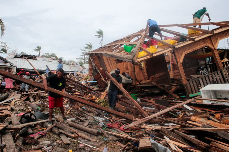 Residents remove debris from their houses destroyed by the passing of Hurricane Iota, in Puerto Cabezas
