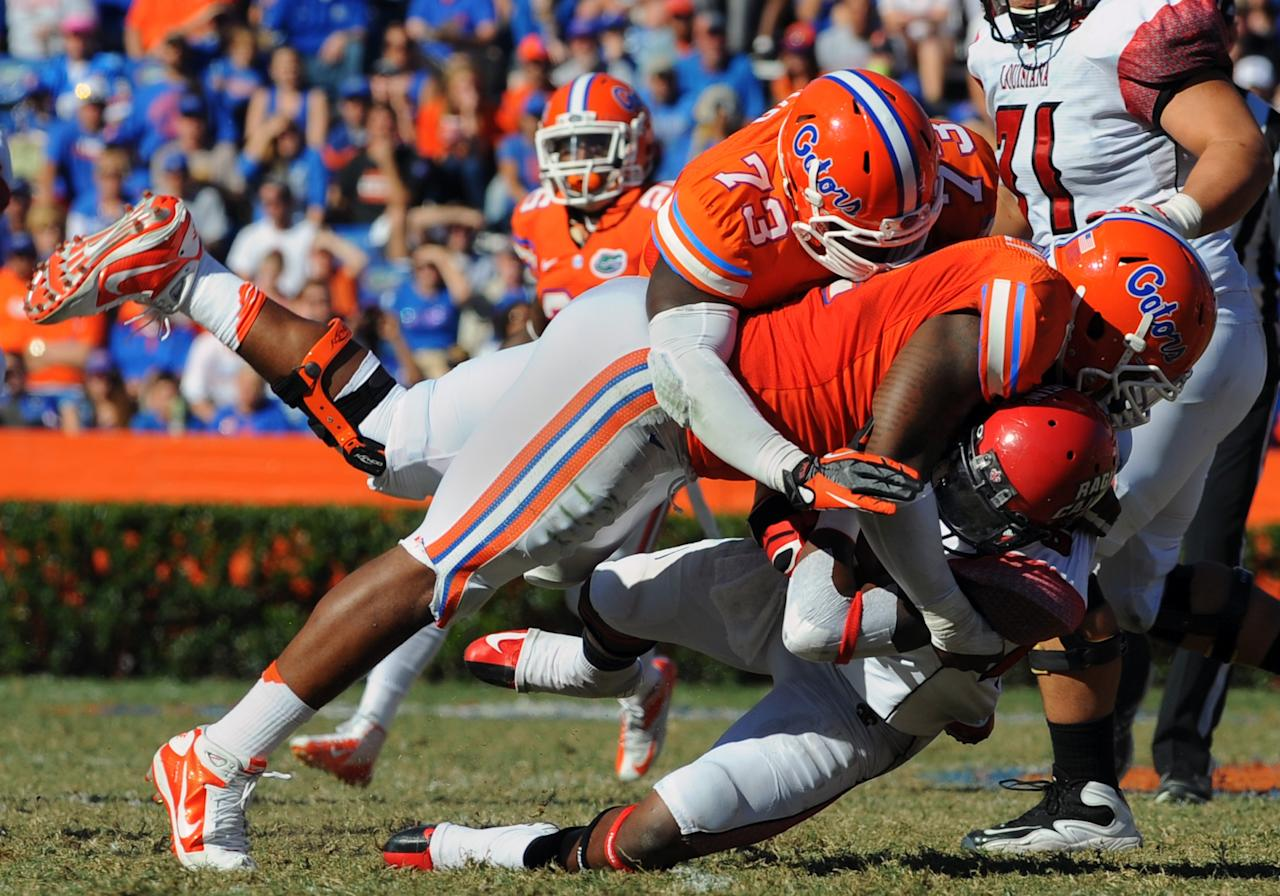 GAINESVILLE, FL - NOVEMBER 10: Defensive lineman Sharrif Floyd #73 of the Florida Gators tackles running back Alonzo Harris #46 of the Louisiana-Lafayette Ragin' Cajuns November 10, 2012 in Gainesville, Florida. Florida won 27 - 20. (Photo by Al Messerschmidt/Getty Images)