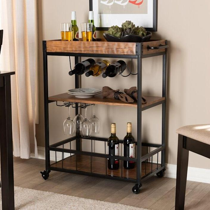 """And if you're looking for somewhere to keep those glasses, this mobile <a href=""""https://www.architecturaldigest.com/gallery/the-29-best-bar-carts-under-dollar500?mbid=synd_yahoo_rss"""" rel=""""nofollow noopener"""" target=""""_blank"""" data-ylk=""""slk:bar cart"""" class=""""link rapid-noclick-resp"""">bar cart</a> has handy compartments to hold his favorite types of liquor, wine glasses, and other drink-making essentials. $195, Wayfair. <a href=""""https://www.wayfair.com/furniture/pdp/sand-stable-raelynn-mobile-metal-bar-cart-w001516041.html"""" rel=""""nofollow noopener"""" target=""""_blank"""" data-ylk=""""slk:Get it now!"""" class=""""link rapid-noclick-resp"""">Get it now!</a>"""