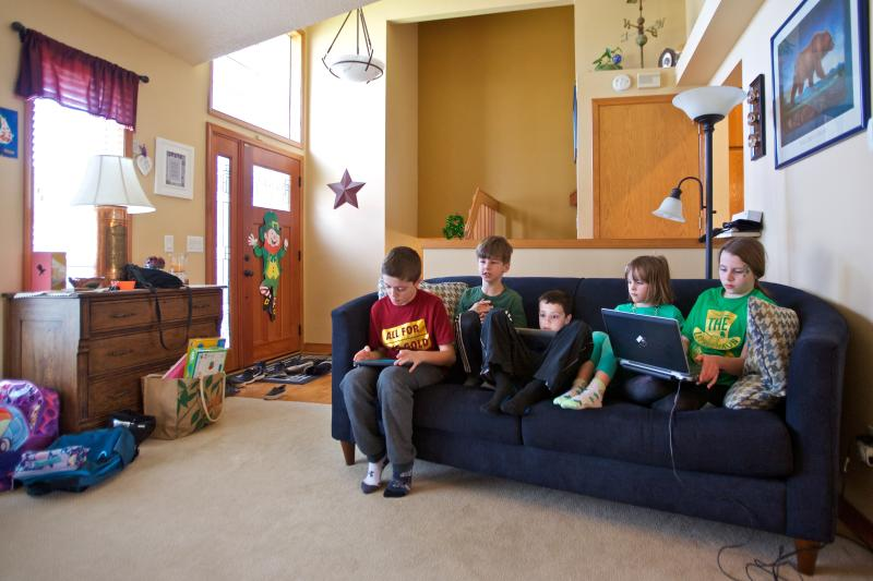 """In this Tuesday, March 17, 2020 photo From left, Mac Collins, age 10, Benitt Reynolds, age 8, Kyson Collins, age 7, Savannah Bergeron, age 6 and Sydney Bergeron, age 10 watch you tube videos sent from their teachers in Vancouver, Wash. Collins mother Renee is a middle school teacher at Thomas Jefferson Middle School and has created a curriculum for some of the neighborhood kids while the schools are closed. """"We're going to have to get creative. It's minute by minute. We don't want them to sit idle and we want to keep their minds busy,"""" she said. (AP Photo/Craig Mitchelldyer)"""