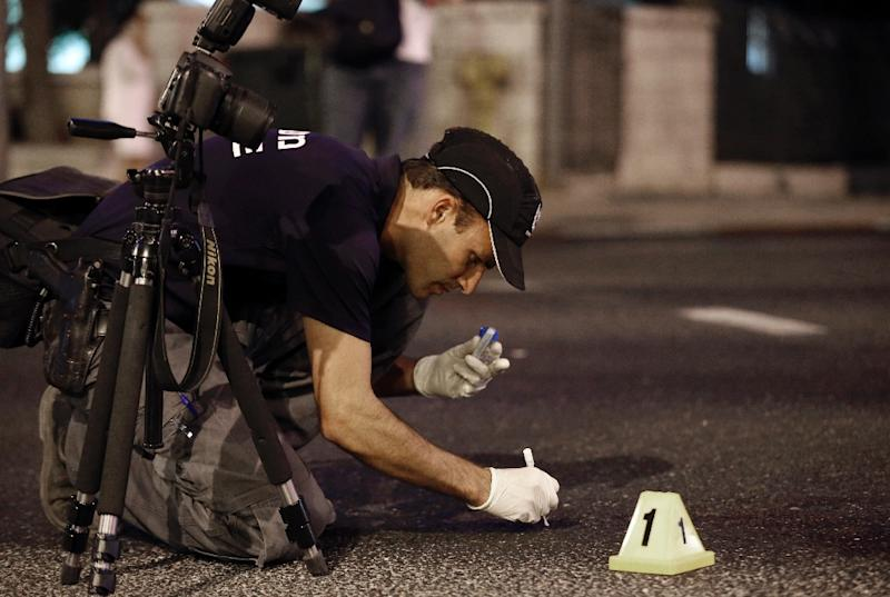 A member of the Israeli police forensic team collects evidence at the site where Yishai Shlissel, an ultra-orthodox Jew, stabbed six people taking part in a Gay Pride march in central Jerusalem on July 30, 2015 (AFP Photo/Thomas Coex)