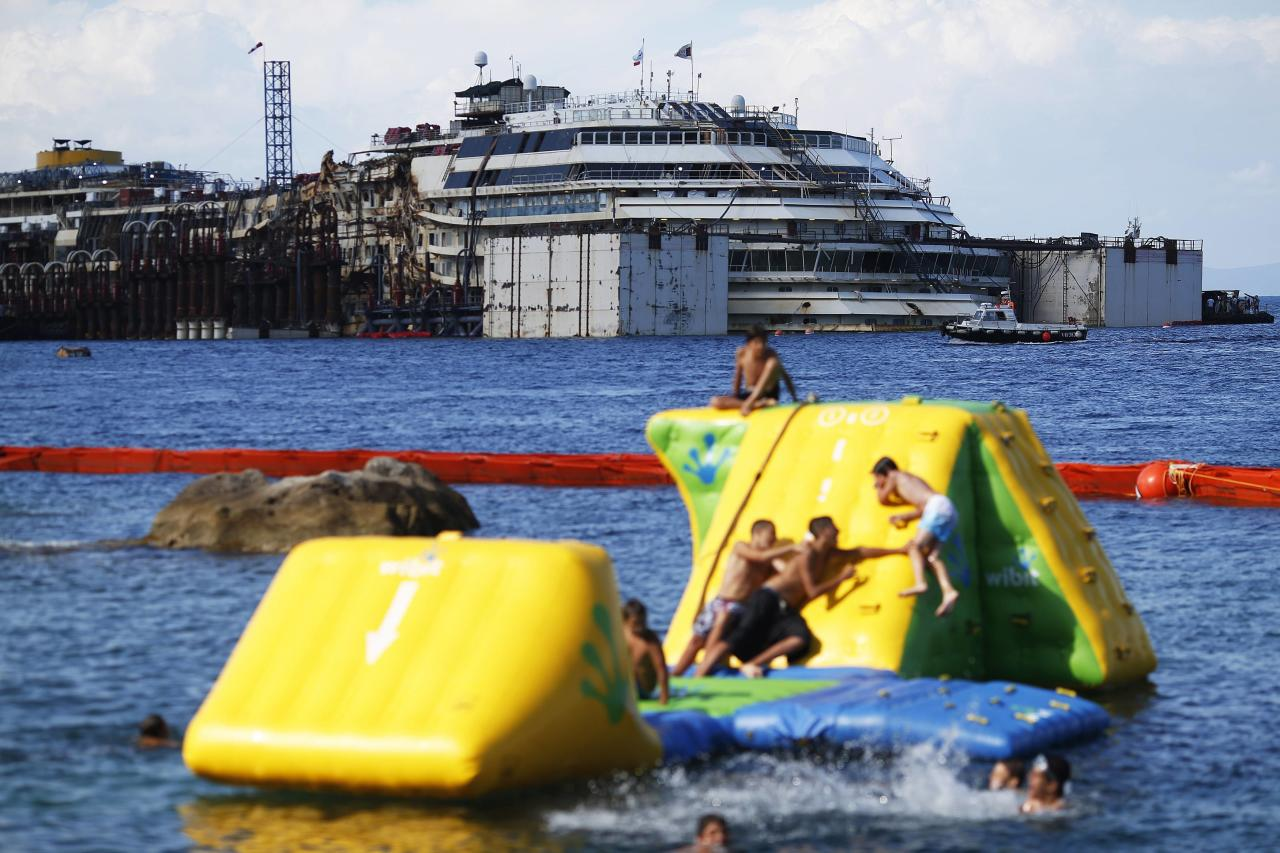 """People dive in front of the cruise liner Costa Concordia at Giglio harbour, Giglio Island July 13, 2014. Italian authorities gave the green light to refloating the wrecked Costa Concordia cruise ship on Saturday, setting the stage for the next step in the largest maritime salvage in history to begin on Monday morning. The defunct luxury liner is due to depart Giglio on July 21, two and a half years after it struck a reef while performing a display manoeuvre to move close to shore and """"salute"""" the port. REUTERS/Alessandro Bianchi (ITALY - Tags: DISASTER TRANSPORT MARITIME)"""