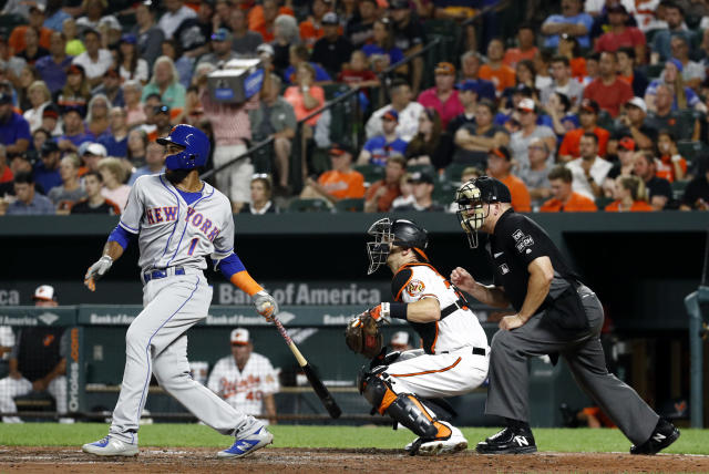 New York Mets' Amed Rosario, left, singles in front of Baltimore Orioles catcher Caleb Joseph and umpire Jeff Nelson in the fifth inning of a baseball game, Tuesday, Aug. 14, 2018, in Baltimore. Jose Bautista scored on the play. (AP Photo/Patrick Semansky)