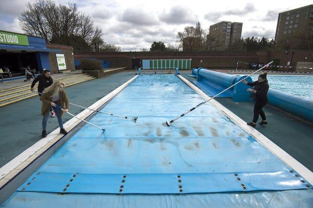 Members of staff clean the cover of the pool during pre-opening preparation and cleaning of Charlton Lido, south London (Kirsty O'Connor/PA)