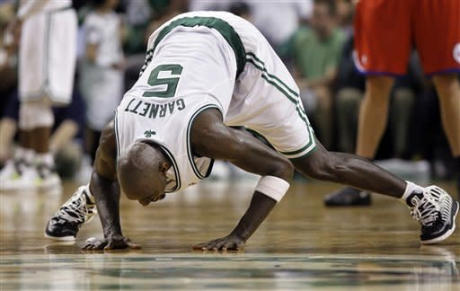 Boston Celtics forward Kevin Garnett bends low on the parquet floor at the end of a timeout in the second quarter of Game 7 against the Philadelphia 76ers in an NBA basketball Eastern Conference semifinal playoff series, Saturday, May 26, 2012, in Boston. (AP Photo/Elise Amendola)