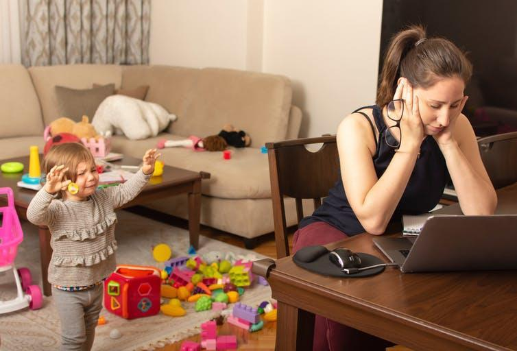 Woman looks at laptop while child cries in background