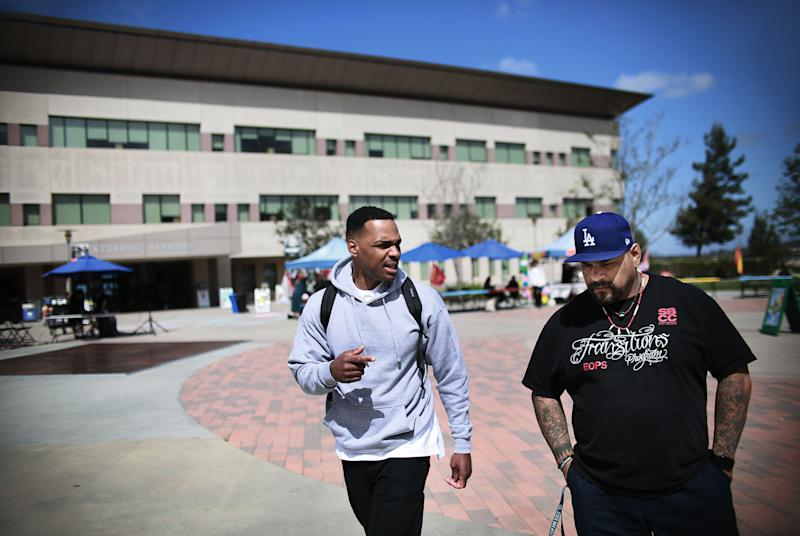 "Tim Jackson and Martin Leyva, both formerly incarcerated students, walk across the Cal State San Marcos campus on Thursday, April 12, 2018. Jackson said that education helped open his eyes to the truth and a better life: ""Truth is the most powerful reality on this side of existence and I have come to learn that education manifests truth."" (Photo: Sandy Huffaker for Yahoo News)"