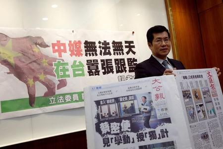 FILE PHOTO: Democratic Progressive Party lawmaker Lo Chih Cheng poses with copies of Hong Kong's Ta Kung Pao and Wen Wei Po newspapers after a news conference in Taipei, Taiwan January 18, 2019. REUTERS/Tyrone Siu/File Photo