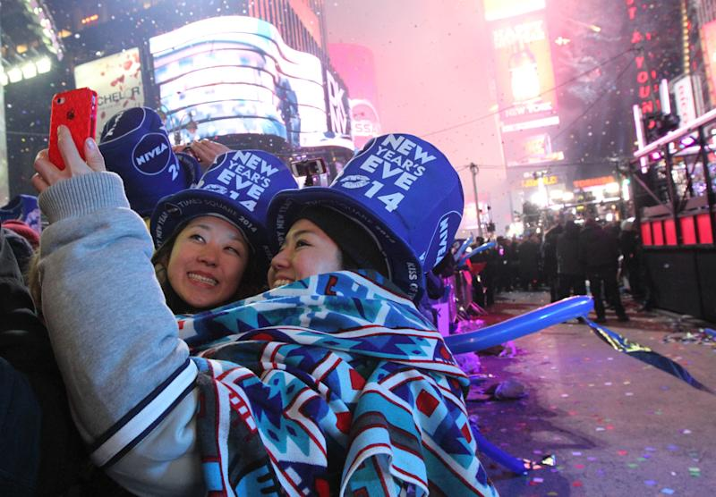 Revelers take part in the festivities in New York's Times Square shortly after midnight New Year's Day Wednesday Jan. 1, 2014. (AP Photo/Tina Fineberg)