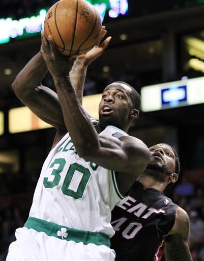Boston Celtics forward Brandon Bass (30) pulls down a defensive rebound in front of Miami Heat forward Udonis Haslem (40) during the first quarter of an NBA basketball game in Boston, Tuesday, April 24, 2012. (AP Photo/Elise Amendola)