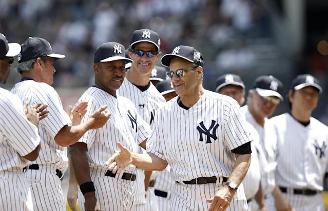 Former New York Yankees greet former Yankees manager Joe Torre, front right, during introductions for the 68th annual Old Timers' Day before the Baltimore Orioles baseball game against the Yankees at Yankee Stadium in New York, Sunday, June 22, 2014. (AP Photo/Kathy Willens)