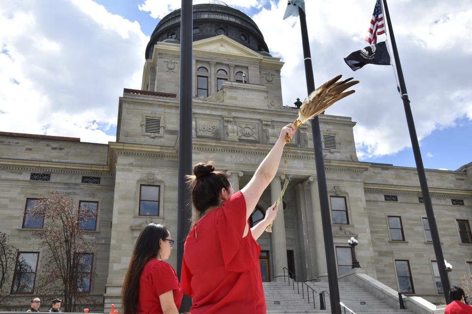 Women wear red to honor missing and murdered indigenous people during a ceremony in front of the Montana state Capitol in Helena, Mont., Wednesday, May 5, 2021. (AP Photo/Iris Samuels)