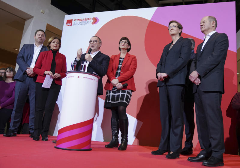 Norbert Walter-Borjans, center left, and Saskia Esken, center right, celebrate winning the vote on the podium as Olaf Scholz, Federal Minister of Finance, right, and Klara Geywitz applaud after the SPD chairmanship vote result, in Berlin, Saturday Nov. 30, 3019. The new leadership will be confirmed at the party conference on December 6. (Kay Nietfeld/dpa via AP)