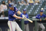 Texas Rangers' Nick Solak hits an RBI sacrifice fly against the Seattle Mariners during the fourth inning of a baseball game Saturday, May 29, 2021, in Seattle. (AP Photo/Elaine Thompson)