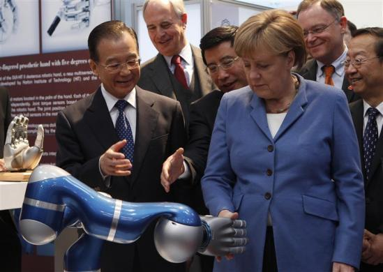 Chinese Premier Wen Jiabao (L) watches as German Chancellor Angela Merkel touches a robotic hand at the stand of Harbin Institute of Technology during their opening tour at the Hanover industrial fair in Hanover, April 23, 2012.