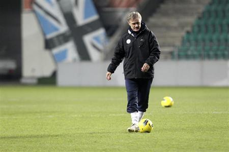 Estonia's national soccer team head coach Tarmo Ruutli plays with the ball as he attends a training session in Tallinn