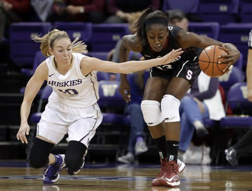 Washington's Kristi Kingma, left, stumbles as she reaches for the ball controlled by Stanford's Chiney Ogwumike during the first half of an NCAA college basketball game Thursday, Feb. 28, 2013, in Seattle. (AP Photo/Elaine Thompson)