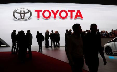 FILE PHOTO - Visitors look at car models on the Toyota stand during the 88th Geneva International Motor Show in Geneva, Switzerland, March 7, 2018. REUTERS/Denis Balibouse
