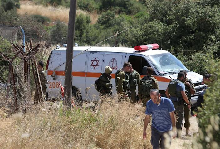 An Israeli ambulance and soldiers are seen outside the house in the Jewish West Bank settlement of Kiryat Arba where a 13-year-old Israeli girl was fatally stabbed, on June 30, 2016 (AFP Photo/Menahem Kahana)