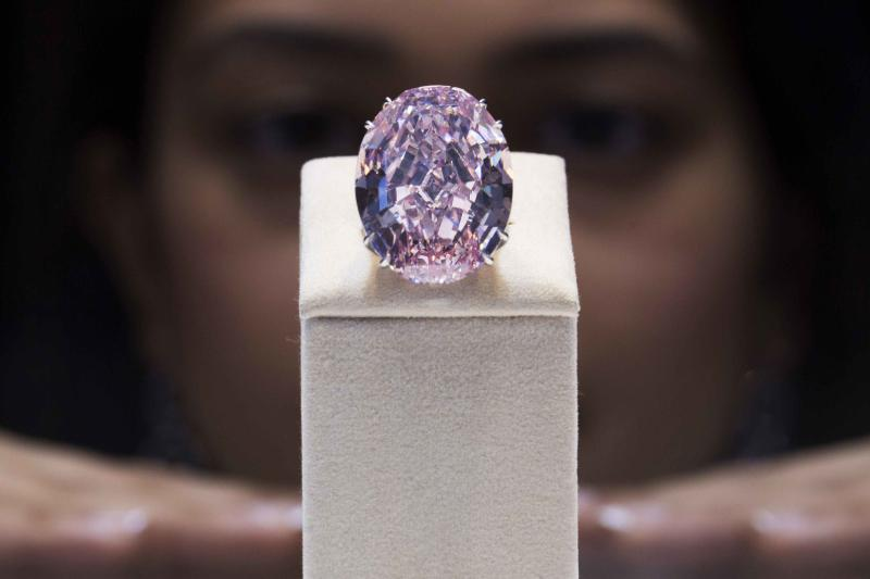 A model poses with the Pink Star diamond during a press preview at Sotheby's in Hong Kong in this file photo taken October 3, 2013. The diamond sold for 76.3 million Swiss francs ($83.02 million) in Geneva November 13, a world record price for a gemstone at auction, Sotheby's said. Perhaps one of the best ways to identify an asset bubble is to watch what the super-rich do with their extra money. REUTERS/Tyrone Siu/Files (CHINA - Tags: SOCIETY WEALTH BUSINESS)