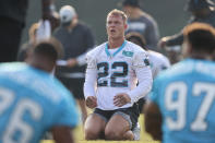 Carolina Panthers running back Christian McCaffrey sits on the field during stretching at the NFL football team's training camp in Spartanburg, S.C., Tuesday, Aug. 10, 2021. (AP Photo/Nell Redmond)