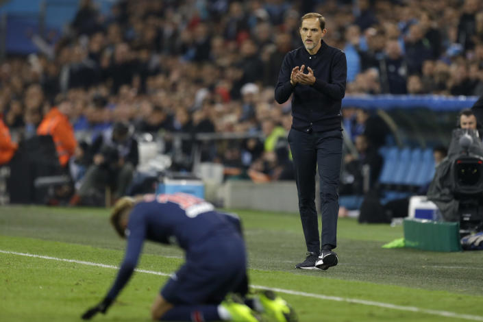 PSG's coach Thomas Tuchel supports PSG's Neymar during the French League One soccer match between Paris-Saint-Germain and Marseille at the Velodrome Stadium in Marseille, France, Sunday, Oct. 28, 2018. (AP Photo/Claude Paris)
