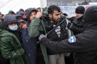 A policeman pushes migrants, one wearing protective equipment against the new coronavirus, as they wait to be relocated during a snowfall at the Lipa camp northwestern Bosnia, near the border with Croatia, Saturday, Dec. 26, 2020. Hundreds of migrants are stranded in a burnt-out squalid camp in Bosnia as heavy snow fell in the country and temperatures dropped during a winter spell of bad weather after fire earlier this week destroyed much of the camp near the town of Bihac that already was harshly criticized by international officials and aid groups as inadequate for housing refugees and migrants.(AP Photo/Kemal Softic)