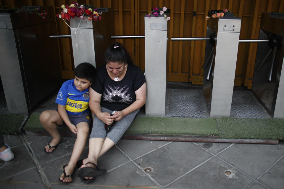 Fans sit near flowers left by mourners in honor of Diego Maradona, at the entrance of the Boca Juniors stadium known as La Bombomera, in Buenos Aires, Argentina, Wednesday, Nov. 25, 2020. The Argentine soccer great who was among the best players ever and who led his country to the 1986 World Cup title before later struggling with cocaine use and obesity, died from a heart attack on Wednesday at his home in Buenos Aires. He was 60. (AP Photo/Natacha Pisarenko)
