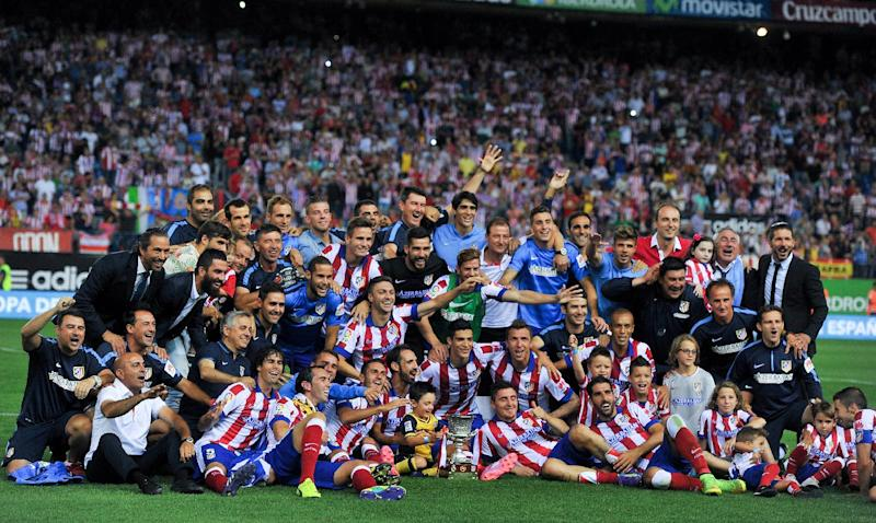 Atletico Madrid's players and staff pose on the pitch with the Super Cup trophy at the end of their Spanish Supercopa second-leg match against Real Madrid, at the Vicente Calderon Stadium in Madrid, on August 22, 2014 (AFP Photo/Dani Pozo)