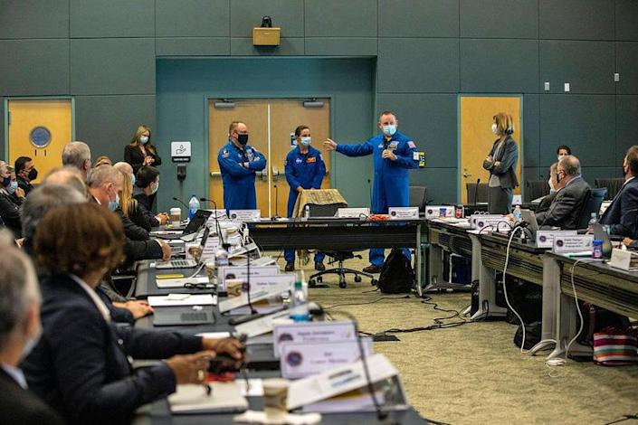 Three astronauts who will fly aboard Boeing's CST-100 Starliner spacecraft for its first crewed flight later this year met with NASA and Boeing mission managers during a flight readiness review to clear the capsule for an unpiloted test flight next week. Left to right: Michael Fincke, pilot Nicole Mann and mission commander Barry