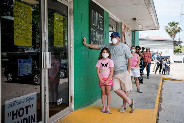 PHOTO: Customers practice social distancing while waiting to buy seafood at Schaefer Seafood in New Orleans, April 11, 2020. (Claire Bangser/AFP via Getty Images, FILE)