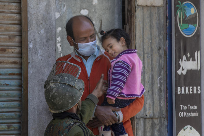 An Indian paramilitary soldier plays with a Kashmiri child during a gunbattle between Indian soldiers and suspected militants in Shopian, south of Srinagar, Indian controlled Kashmir, Friday, April 9, 2021. Seven suspected militants were killed and four soldiers wounded in two separate gunfights in Indian-controlled Kashmir, officials said Friday, triggering anti-India protests and clashes in the disputed region. (AP Photo/ Dar Yasin)