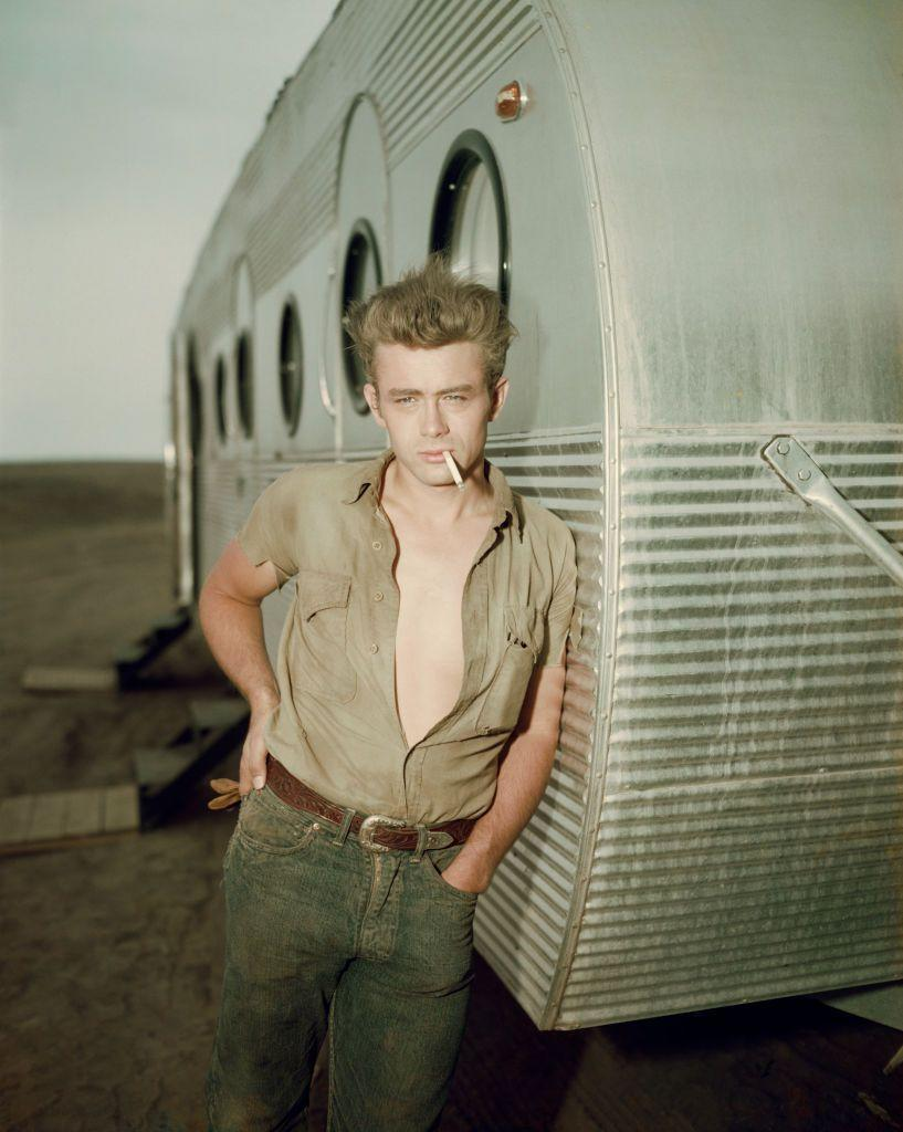 <p>Here, Dean is seen leaning against his dressing trailer on the set of <em>Giant.</em></p>