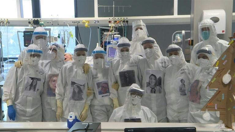 Italian health care workers display their faces on protective gear to reassure patients