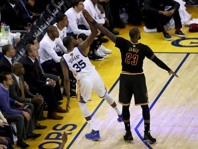 "<a class=""link rapid-noclick-resp"" href=""/nba/players/4244/"" data-ylk=""slk:Kevin Durant"">Kevin Durant</a> and LeBron James meet between the lines. (Getty Images)"