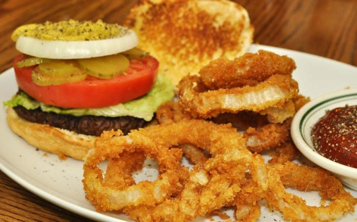 A hamburger and onion rings on a plate.