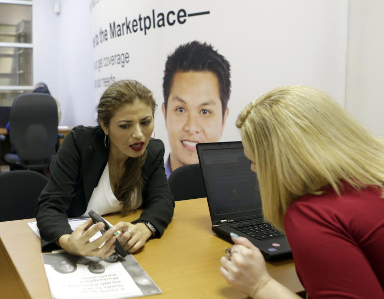 In this Friday, Dec 20, 2013 photo, in Johanna Diaz, left, points out information to Senior Certified Enrollment Specialist Marlene Nesmith at a Healthcare Marketplace office in Miami. Diaz, who had already signed up, visited the office to make sure she was enrolled. (AP Photo/Alan Diaz)