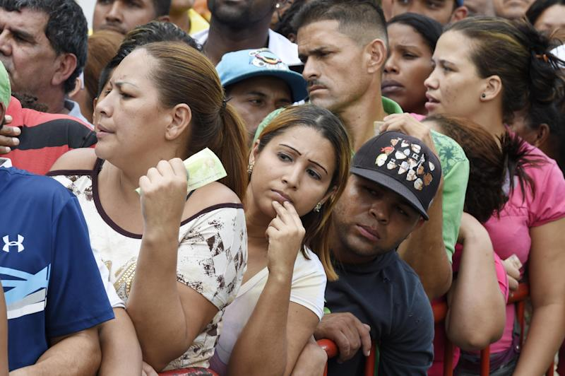 People queue to buy chicken on January 24, 2015, at a Caracas street market in Venezuela with long, everyday waits for things as basic as diapers, coffee and soap (AFP Photo/Juan Barreto )