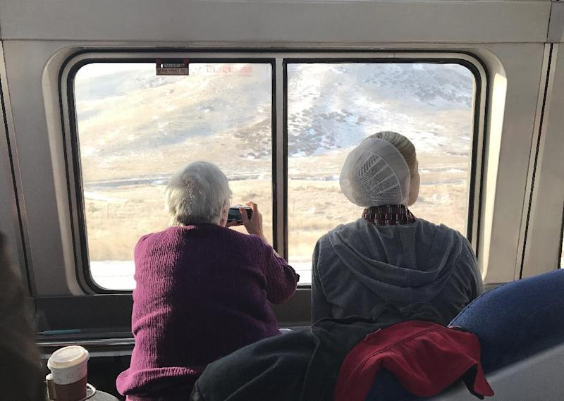 In this photo taken on on Jan. 26, 2017, two women take photos of the Sierra Nevada mountains on the California Zephyr train. AP Tampa correspondent Tamara Lush spent 15 days traveling via train across the U.S. as part of Amtrak's residency program, designed for creative professionals to spend time writing on the rails. She spoke with dozens of people _ fellow travelers, friends and family waiting for loved one at stations, train workers _ and filed occasional dispatches for the Tales on a Train project. (AP Photo/Tamara Lush)