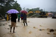 Heavy machinery removes debris from a road affected by a flooding caused by rains from Storm Eta, in Toyos