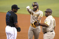 San Diego Padres' Fernando Tatis Jr., center, gestures after hitting a single as Miami Marlins first baseman Jesus Aguilar (24) looks on during the third inning of a baseball game, Saturday, July 24, 2021, in Miami. Padres first base coach Wayne Kirby, right, looks on. (AP Photo/Lynne Sladky)