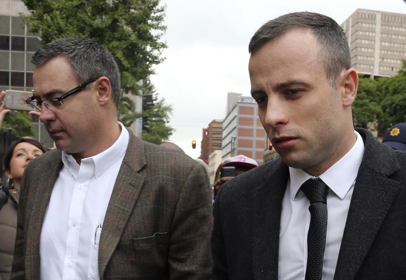 Oscar Pistorius, right, accompanied by relatives arrives at the high court in Pretoria, South Africa, Monday, April 14, 2014. Pistorius is charged with murder for the shooting death of his girlfriend, Reeva Steenkamp, on Valentines Day in 2013. (AP Photo/Themba Hadebe)