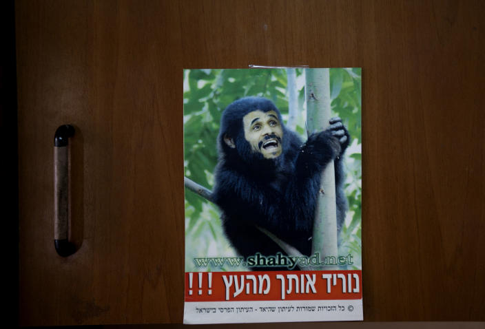 """In this photograph made on Sunday, Feb. 12, 2012, a poster of the Islamic Republic of Iran President Mahmoud Ahmadinejad represented as a monkey displayed in the print house of Kamal Penhasi, the Iranian-born editor of Shahyad, the only Persian-language magazine published in Israel In the israeli town of Holon. The sign reads in Hebrew: """"We'll take you down from the tree"""".(AP Photo/Oded Balilty)"""