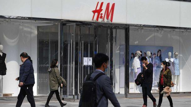 PHOTO: People walk past an H&M store in Beijing on March 25, 2021. (Greg Baker/AFP via Getty Images)