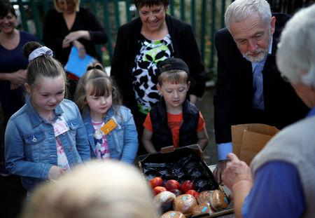 Britain's opposition Labour party leader, Jeremy Corbyn, helps fill childrens packed lunches outside the Hope Centre in Bolton, Britain August 17, 2017. REUTERS/Phil Noble