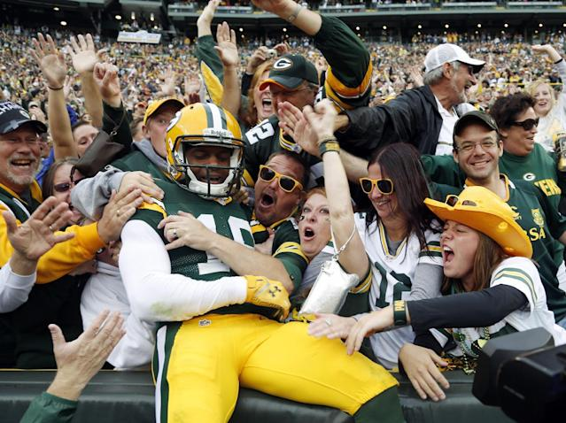 Green Bay Packers' Randall Cobb celebrates with fans after catching a touchdown pass during the first half of an NFL football game against the Washington Redskins Sunday, Sept. 15, 2013, in Green Bay, Wis. (AP Photo/Tom Lynn)