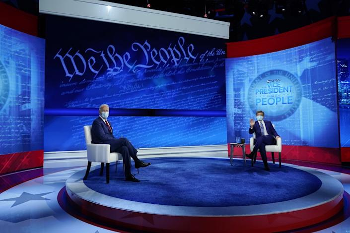 Joe Biden in a mask sits on a town hall stage across from ABC host George Stephanapoulos