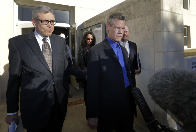 Entertainer Randy Travis, right, exits Grayson County Courthouse with attorney Larry Friedman, left, and other members of his legal team Thursday, Jan. 31, 2013, in Sherman, Texas. Travis plead guilty to driving while intoxicated in a plea agreement with the court and will pay a $2,000 fine and serve a two year probation. (AP Photo/Tony Gutierrez)