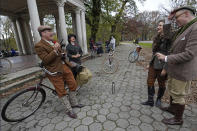 From left, Mick Burgess and Eden Atencio laugh with Michelle Coursey and Matthew Karl Gale as they sip tea and champagne during a stop on the 2020 Brooklyn Tweed Ride, an event in which participants wear vintage clothing and ride classic bicycles on a loop of Prospect Park, Sunday, Nov. 15, 2020, in the Brooklyn borough of New York. The Brooklyn ride is one of several similar events held in cities around the world. (AP Photo/Kathy Willens)